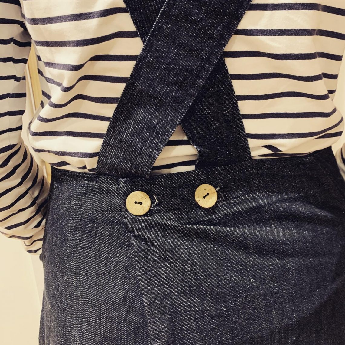 An image of the back of a denim dress where the straps cross over and are closed with wooden badges