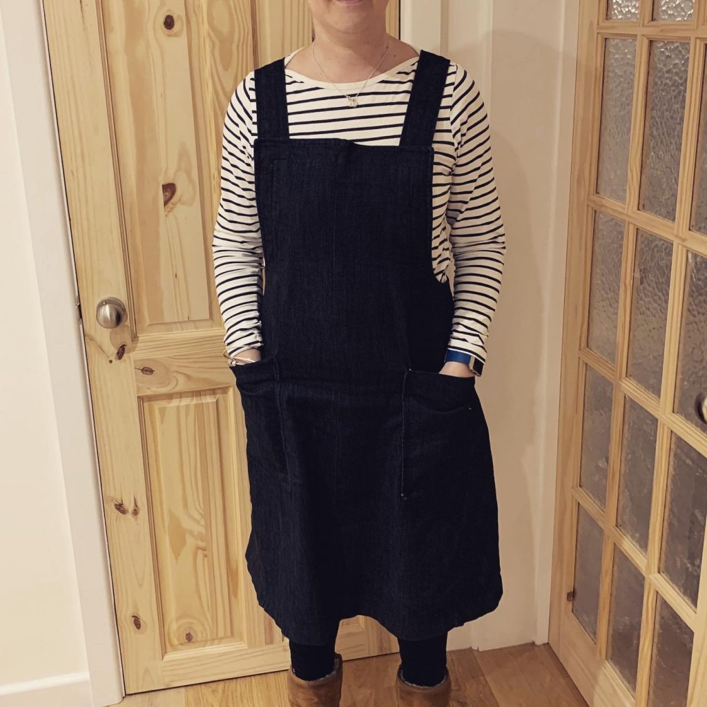 A white woman standing in front of a wooden door wearing a denim pinafore dress and a stripy top