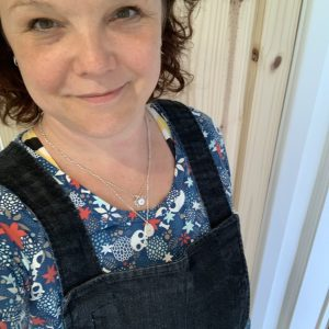 Rosie is wearing a denim pinafore with a blue, red and white long-sleeved t shirt underneath.