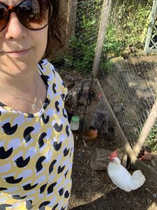 Rosie is wearing a yellow t-shirt with black and white chickens on it, standing in front of three chickens
