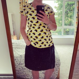 Rosie wearing a yellow t shirt with chicken on, and a denim skirt for me made may 2020 week 3