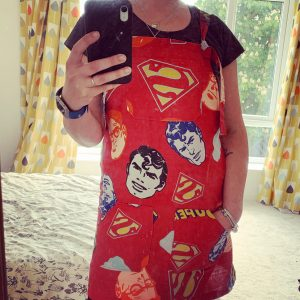 Rosie wearing a red pinafore with superman on it, made from an old duvet cover for me made may 2020 week 3