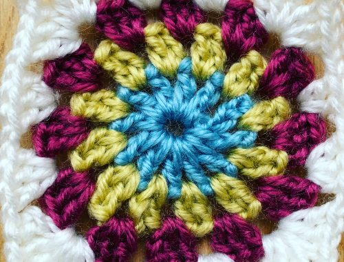 A crochet square, blue centre, yellow and red with a white border ready for a sunburst granny blanket