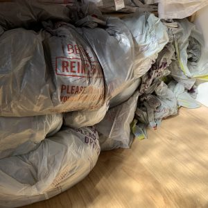 a huge pile of grey carrier bags