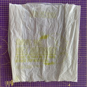 A grey plastic bag with the handles and bottom cut off ready for making plarn