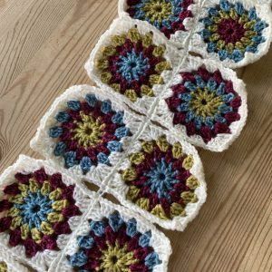 The beginnings of a sunburst granny blanket. Blue, red and yellow granny squares with white borders