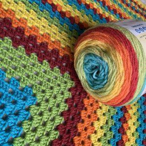 Lockdown blanket dilemma: a new ball of rainbow yarn on top of a crocheted blanket