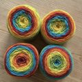 four large balls of yarn in rainbow colours