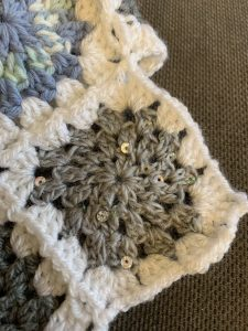 January in blanket form: a granny square made using grey yarn with sequins on to represent the rain