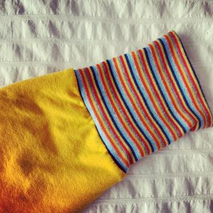 The sleeve of a bright yellow sweatshirt with a rainbow cuff