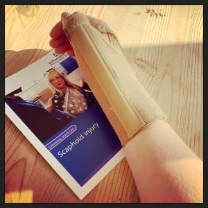 a right wrist wearing a splint and an NHS leaflet about scaphoid injury.