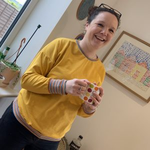 Rosie wearing her bright yellow Driftwood Dolman sweatshirt