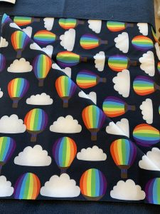 Navy blue fabric printed with clouds and rainbow hot air balloons ready for rosie's latest make a woodland wanderer