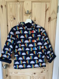 Rosie's latest make - a woodland wanderer. A navy blue coat with rainbow hot air balloons and cloud printed on it. The four buttons are different rainbow colours.