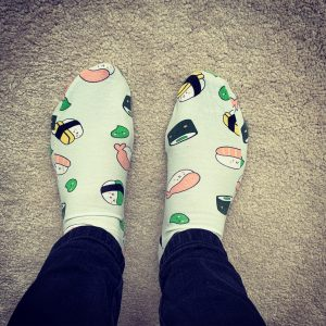 A picture of feet wearing green socks with cartoon sushi on them