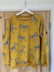 A mustard yellow sweatshirt with zebras on it