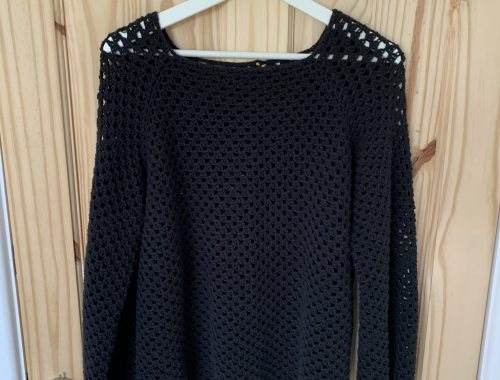 Rosie's latest make: granny go round jumper. A black crochet jumper having on the back of a wooden door.