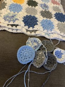 Sky blanket 2021 may update. Rosie has crochet small circles in various shades of grey and blue. They are waiting to be attached to the main blanket.